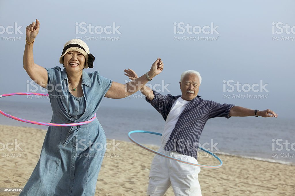 Middle-Aged Couple Hula Hooping stock photo