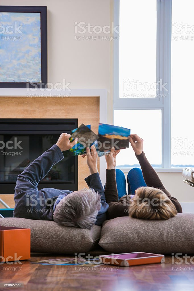 Middle-aged couple on floor looking at photographs stock photo