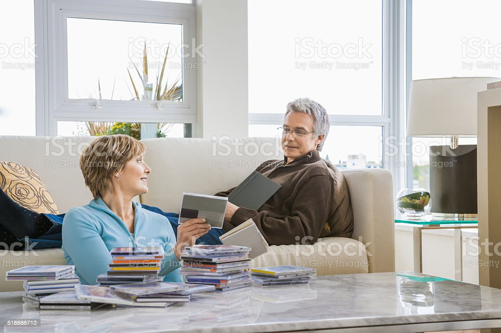 Middle-aged couple relaxing in living room stock photo