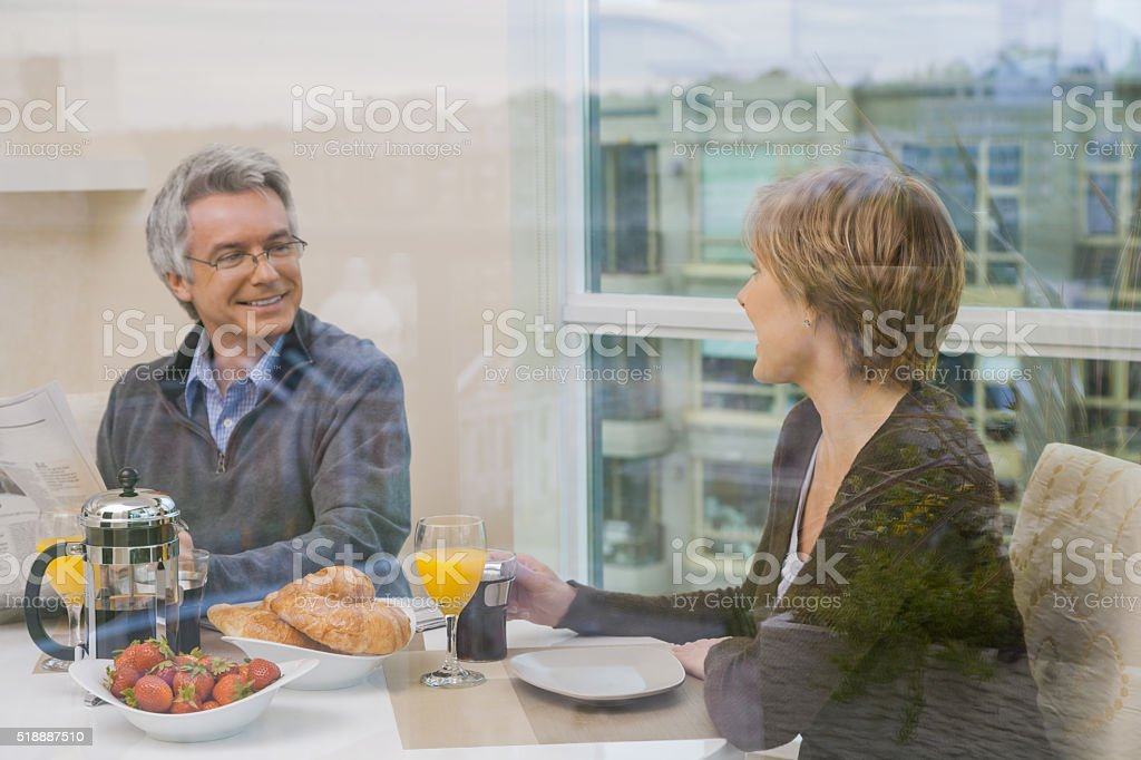 Middle-aged couple relaxing over breakfast stock photo