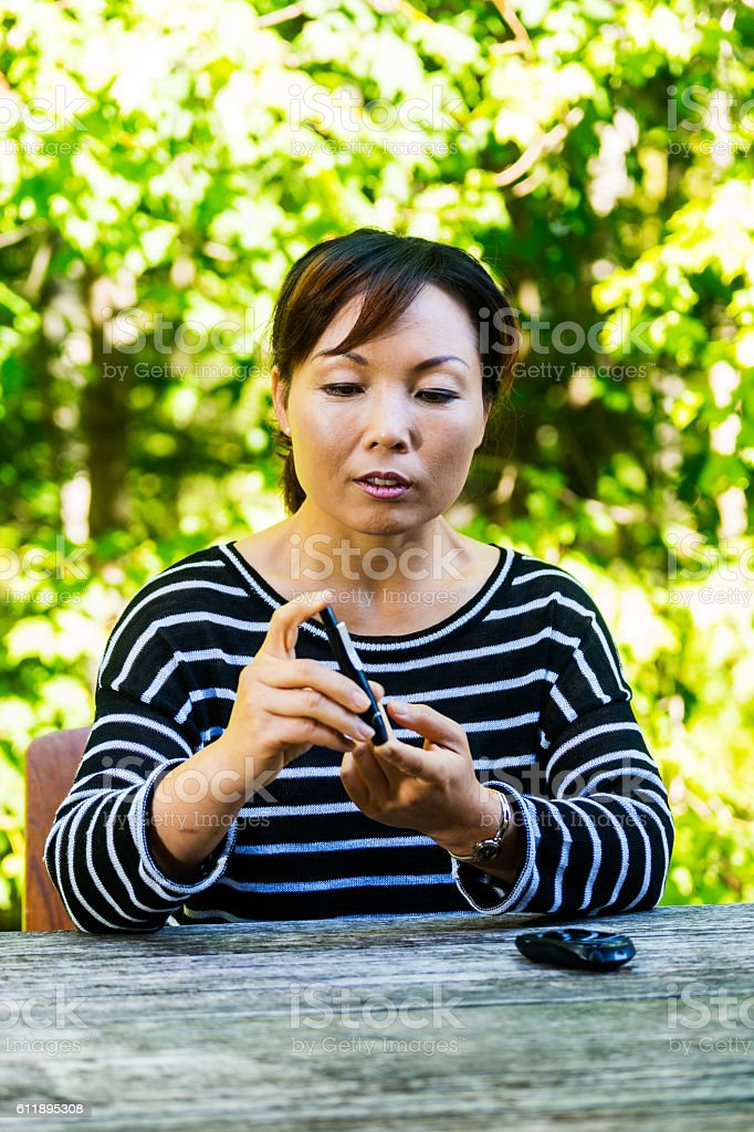 Middle-aged diabetic woman of Asian descent checking her blood stock photo