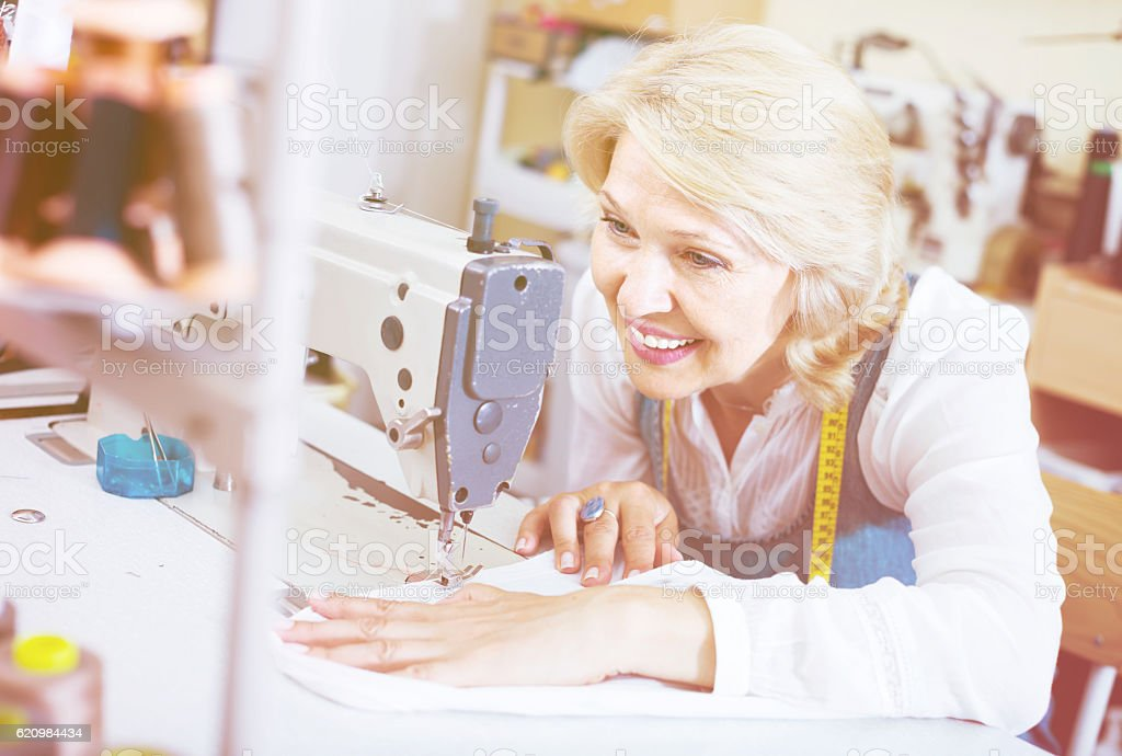 middle-aged female tailor using sewing machine stock photo