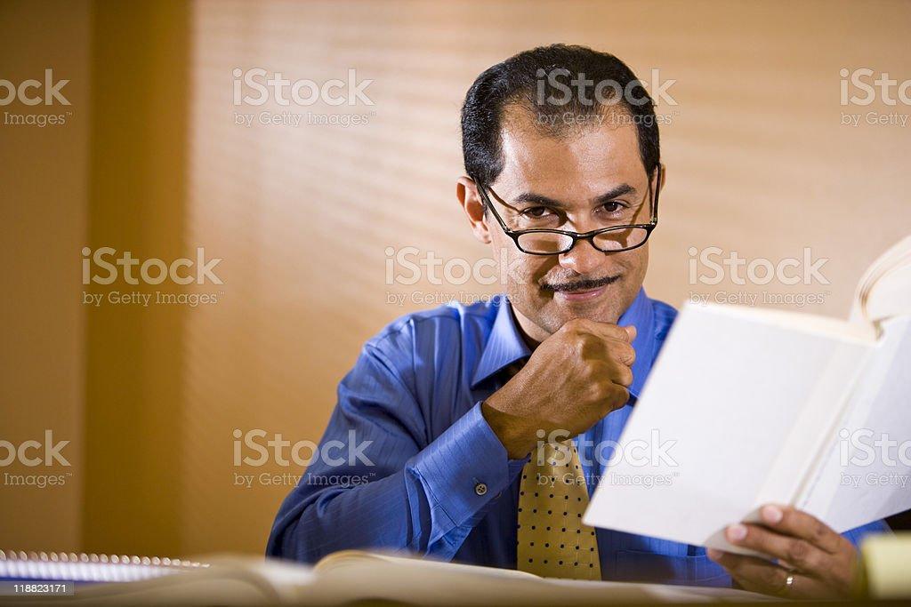 Hispanos empresario de mediana edad trabajando en la oficina, libro de lectura foto de stock libre de derechos