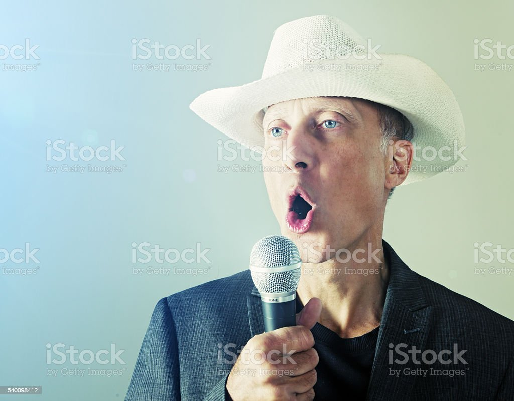 Middle-aged male country  music singer or karaoke enthusiast, with microphone stock photo