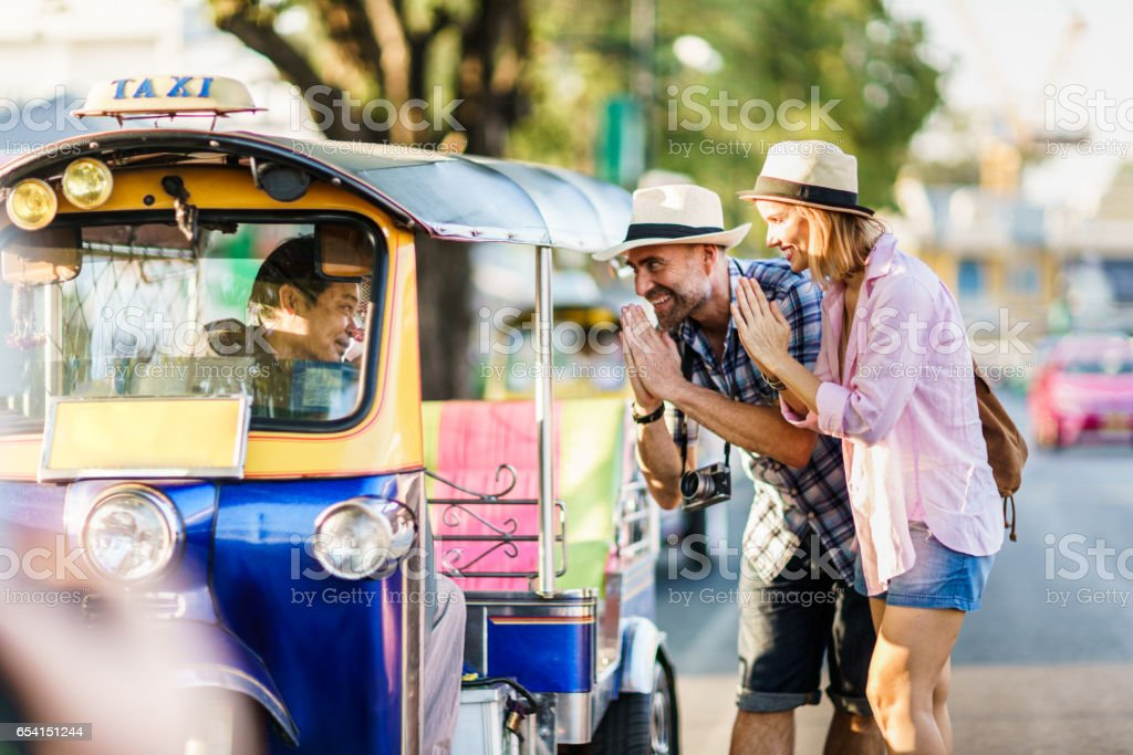 Middle-aged man and his companion handsome blond lady on a tuk-tuk ride in Bangkok stock photo