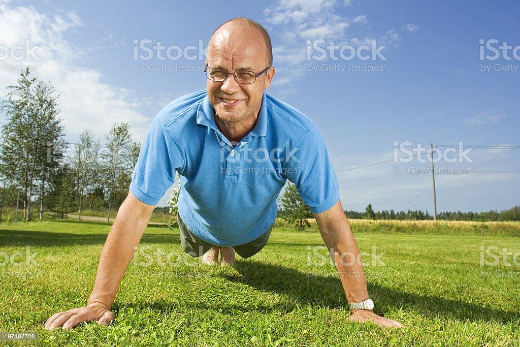 Middle-aged man doing push-ups royalty-free stock photo