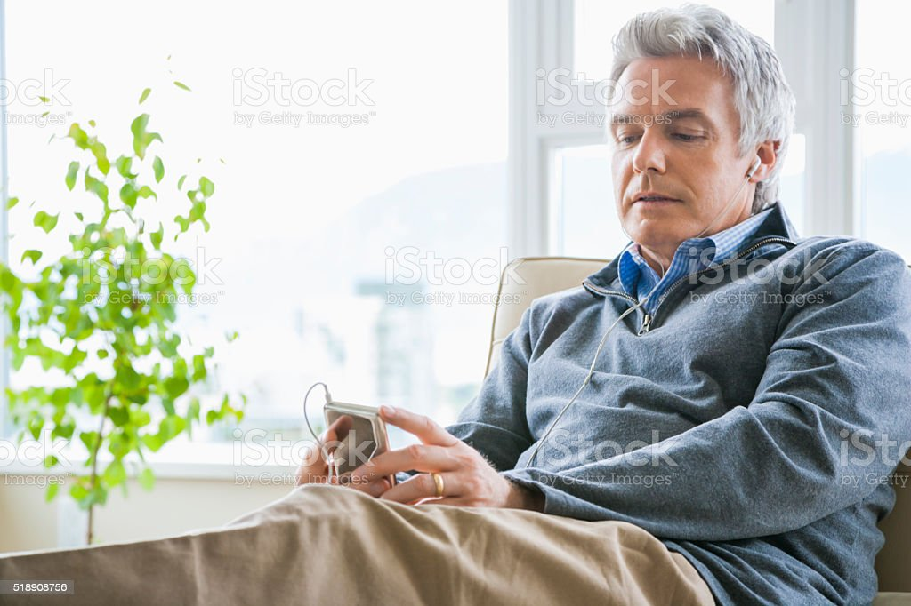 Middle-aged man listening to MP3 player stock photo