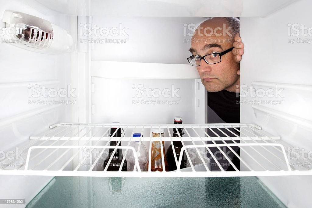 Middle-aged man opens a fridge stock photo