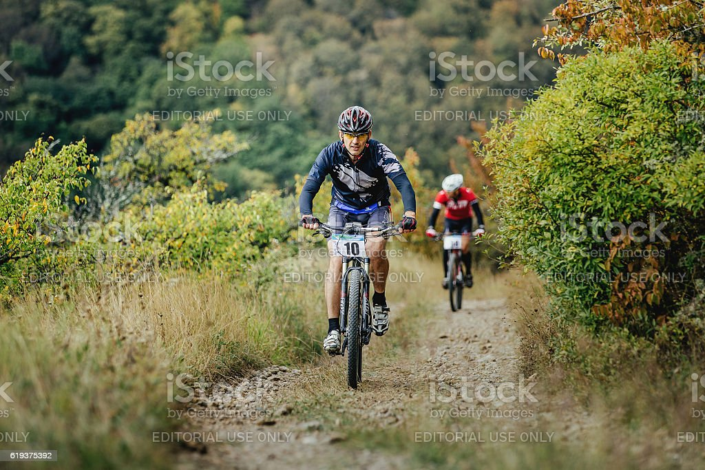 middle-aged man racer cyclist riding uphill stock photo