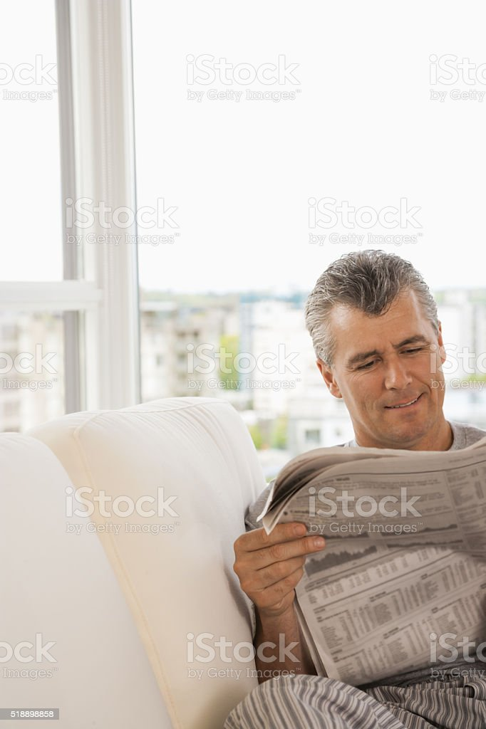 Middle-aged man reading newspaper on sofa stock photo