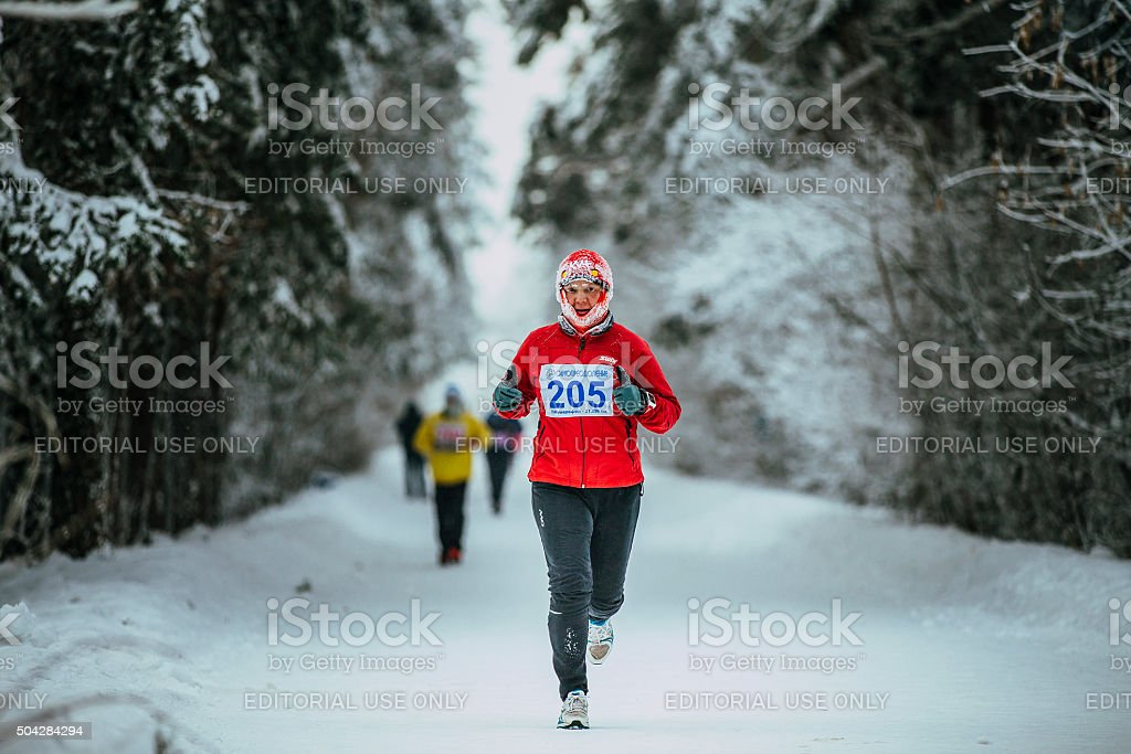 middle-aged man runner while running in cold weather stock photo