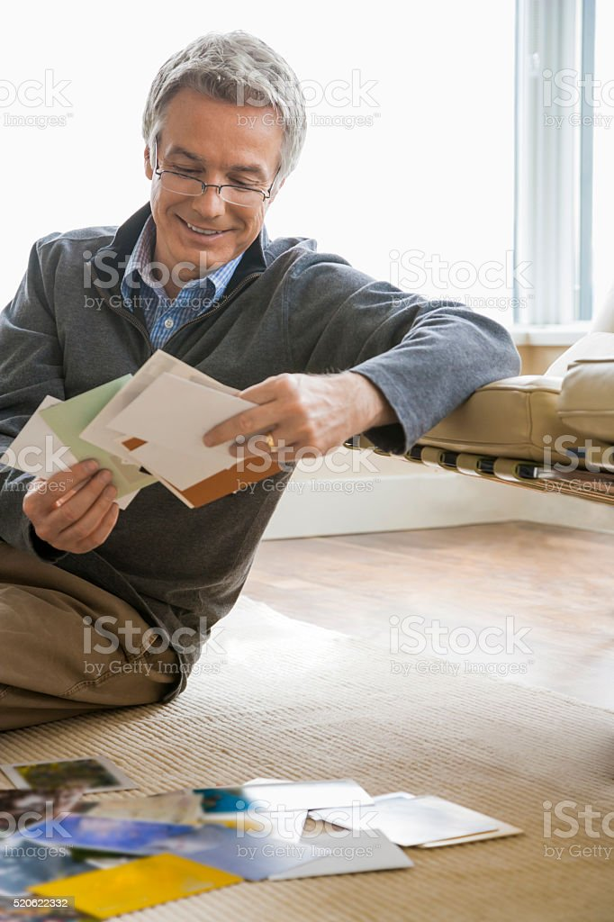 Middle-aged man sitting on floor looking at postcards stock photo
