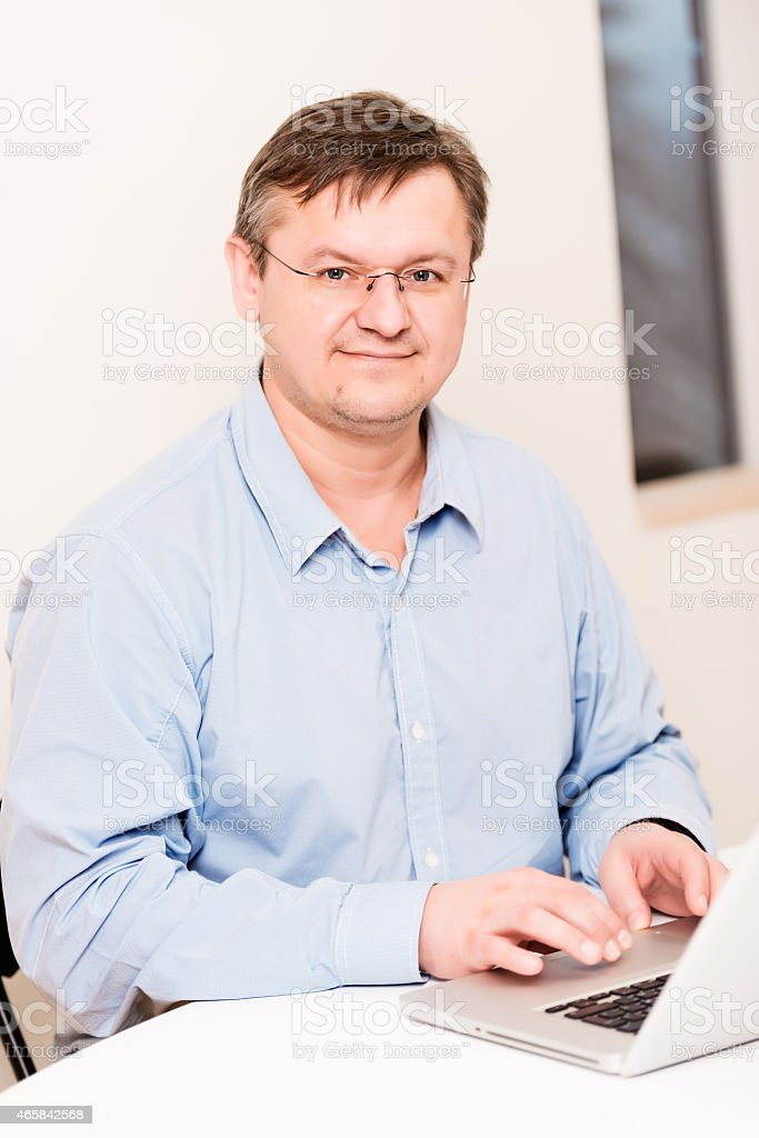 Middleaged man smiling at office stock photo