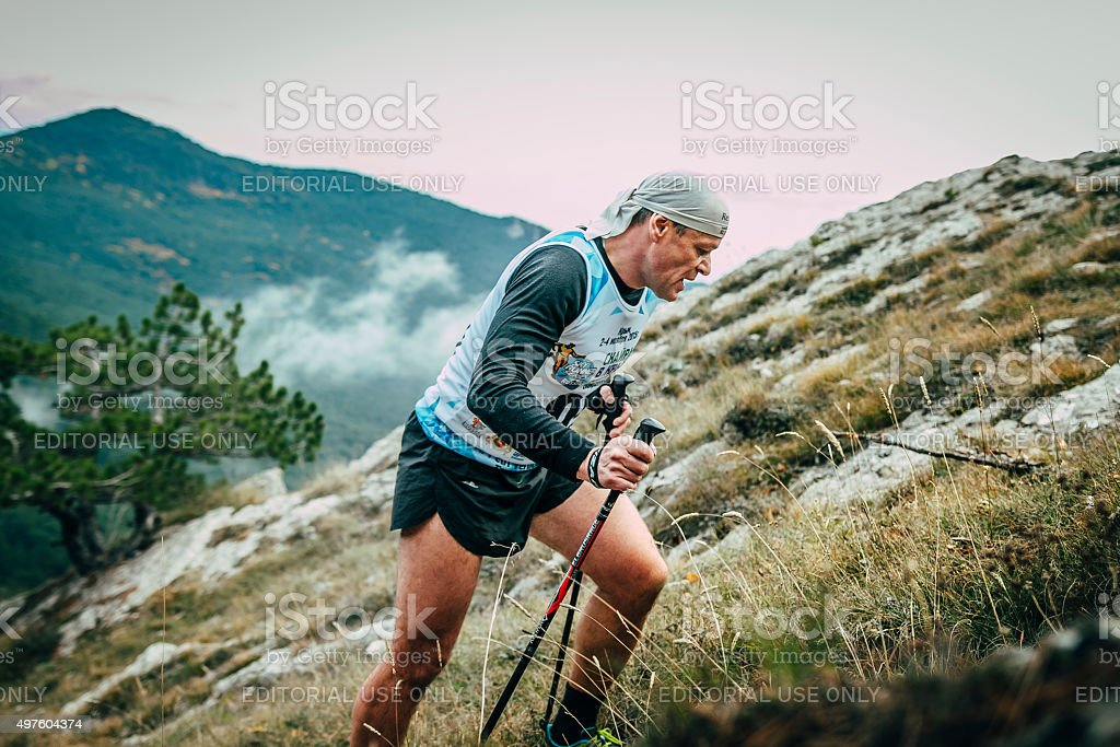 middle-aged man with walking sticks is on side of mountain stock photo