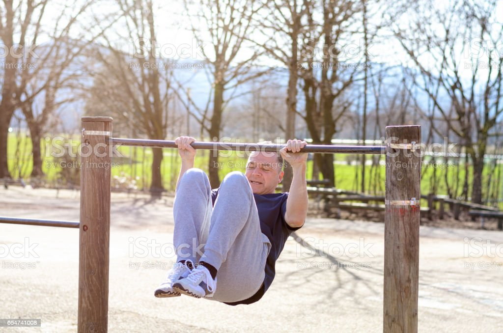 Middle-aged man working out on a horizontal bar stock photo