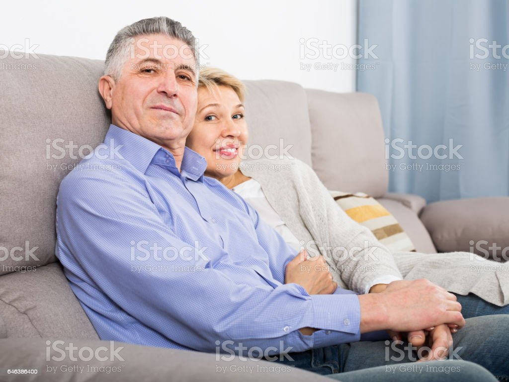 middle-aged married couple in house are warmly reconciled after quarrel stock photo