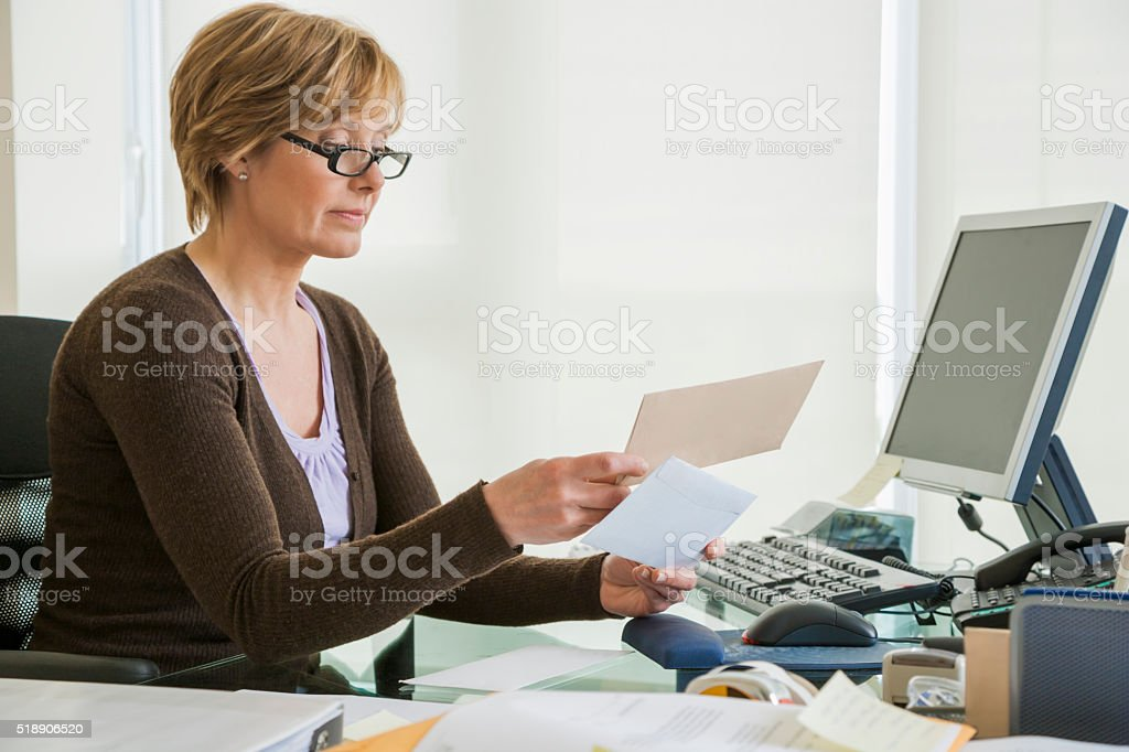 Middle-aged woman looking at bills at computer stock photo