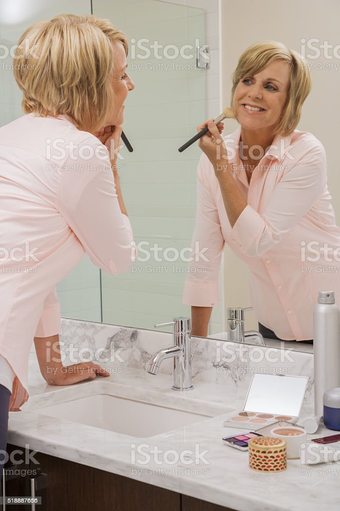 Middle-aged woman putting on makeup stock photo