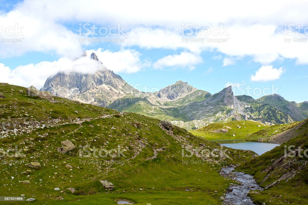 Midi d'Ossau peak behind another mountain and a lake stock photo