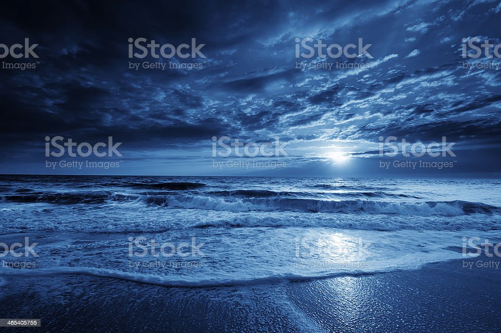 Midnight Blue Coastal Moonrise With Dramatic Sky and Rolling Waves stock photo