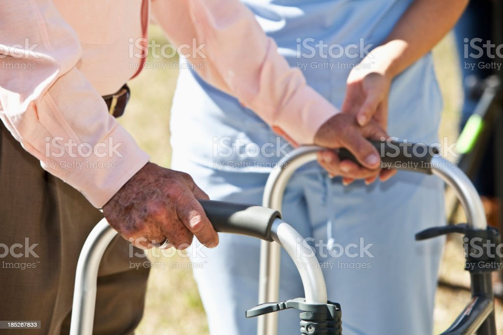 Midsection, healthcare worker helping senior man with walker stock photo