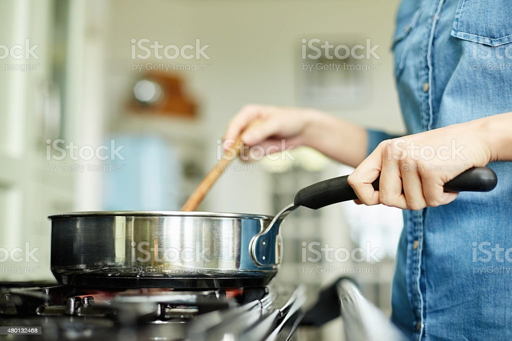 Midsection image of woman cooking food in pan stock photo