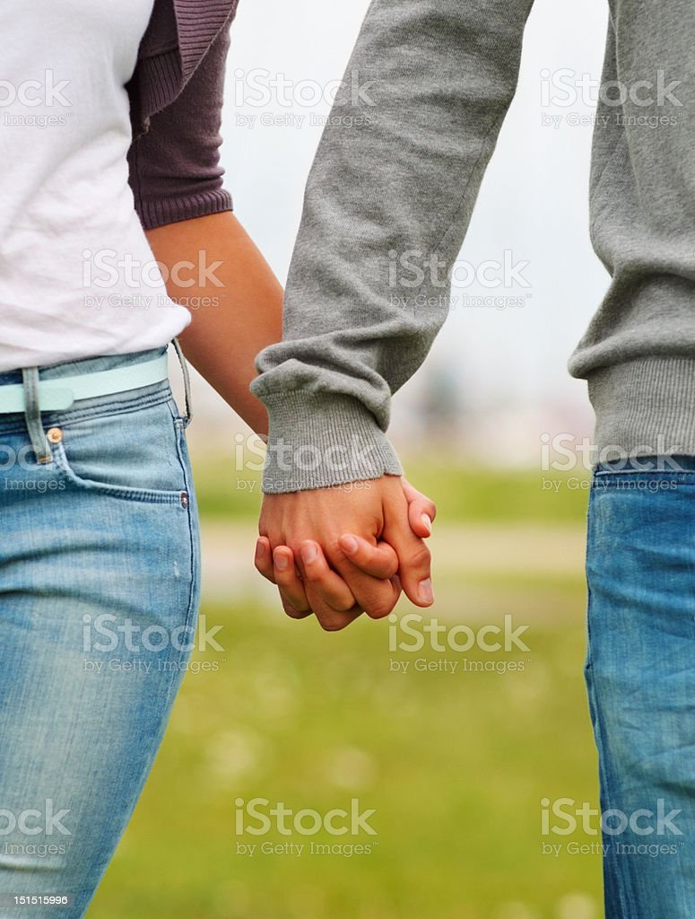 Midsection of a couple holding hands royalty-free stock photo
