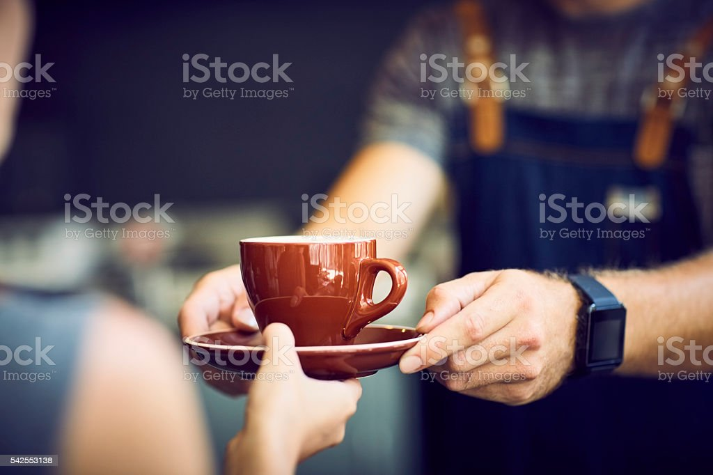 Midsection of barista giving brown cup to waitress stock photo