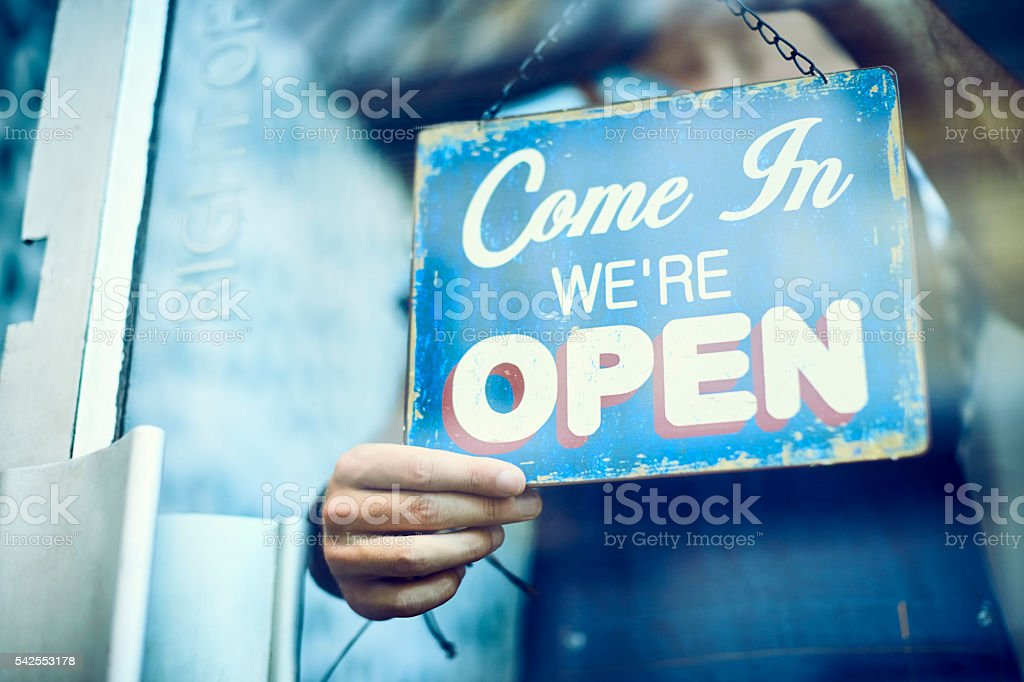 Midsection of barista hanging an open sign stock photo