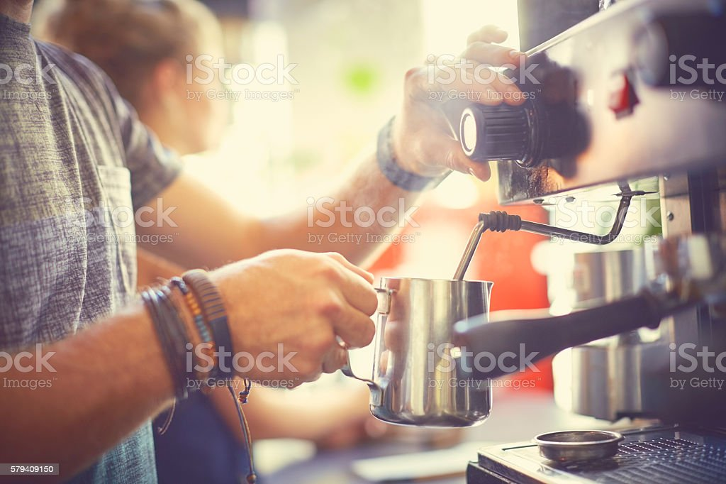 Midsection of barista steaming milk in jug stock photo