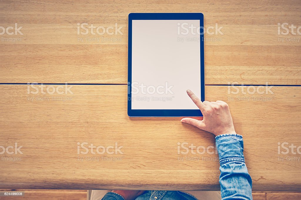 Midsection of blogger using digital tablet at wooden table stock photo
