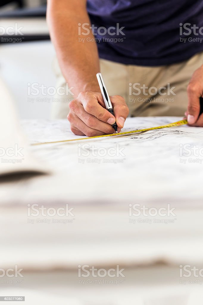 Midsection of businessman drawing on paper stock photo