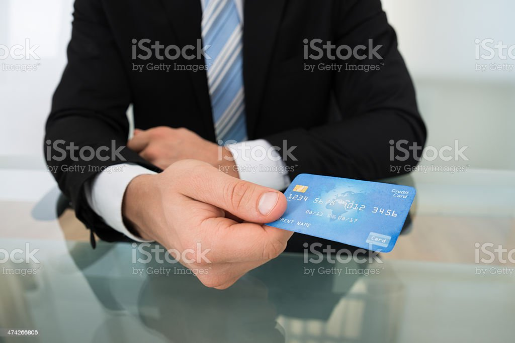 Midsection Of Businessman Giving Credit Card stock photo