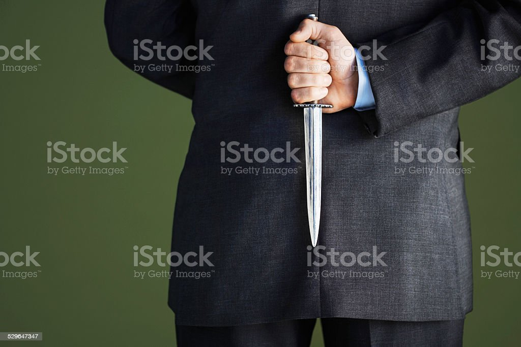 Midsection Of Businessman Holding Knife Behind Back stock photo
