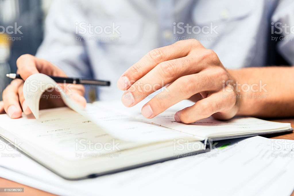 Midsection of businessman turning notepad's page stock photo