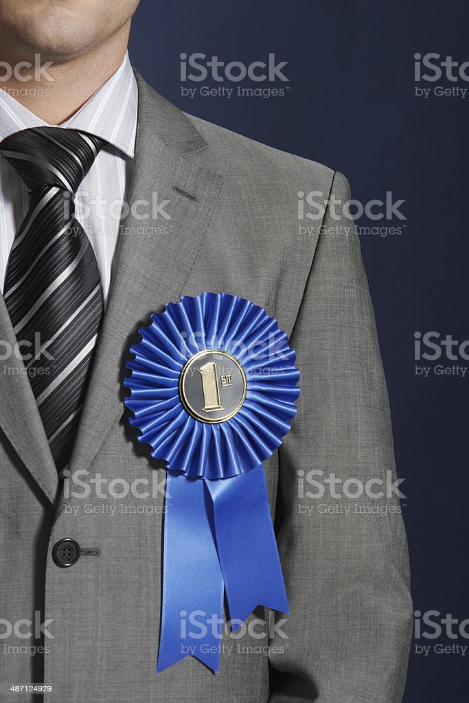 Midsection Of Businessman Wearing Blue Ribbon On Lapel royalty-free stock photo