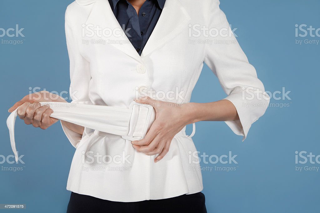 Midsection Of Businesswoman Adjusting Belt royalty-free stock photo