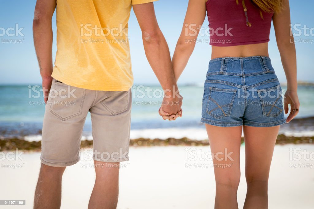 Midsection of couple holding hands at beach stock photo