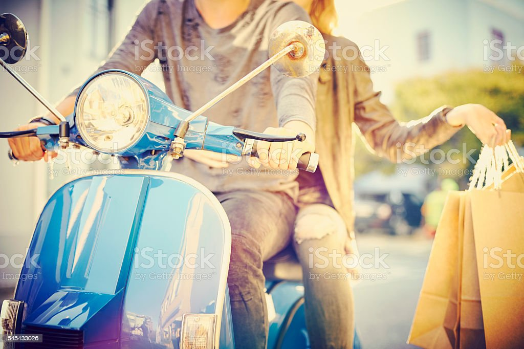 Midsection of couple with bags riding scooter stock photo