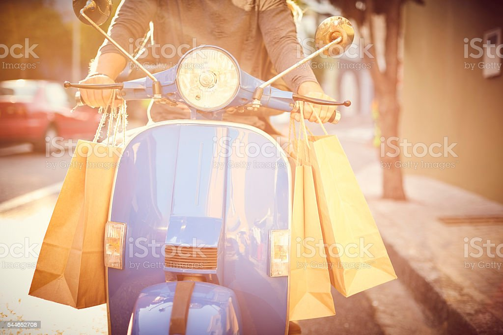 Midsection of couple with shopping bags on motor scooter stock photo
