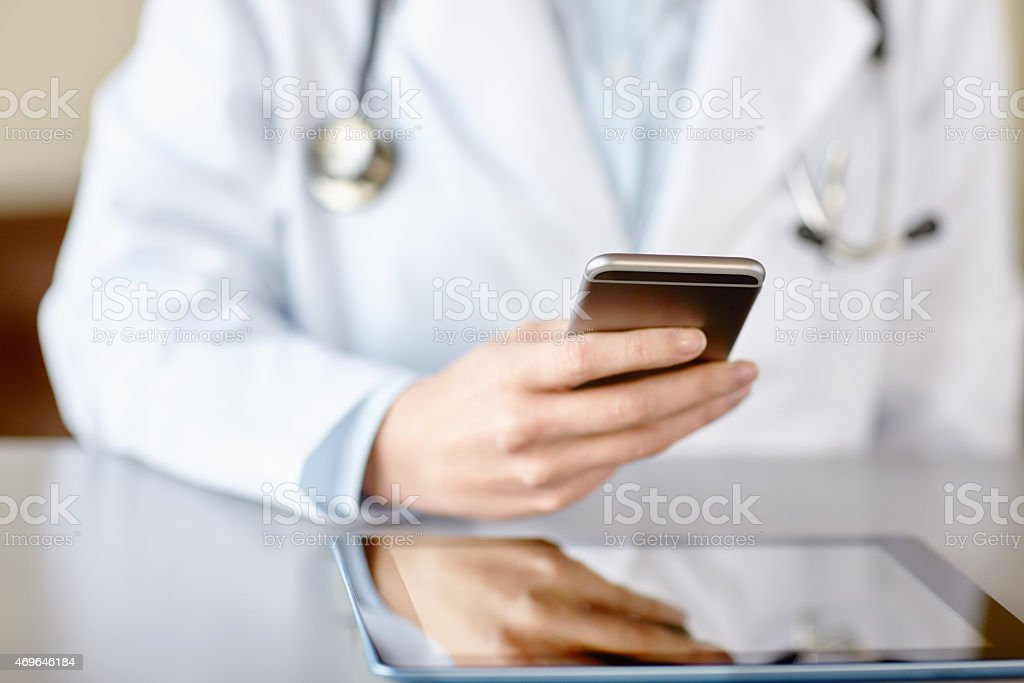 Midsection of doctor text messaging on smart phone in clinic stock photo