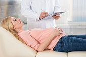 Midsection Of Doctor Writing Notes By Pregnant Woman In Hospital