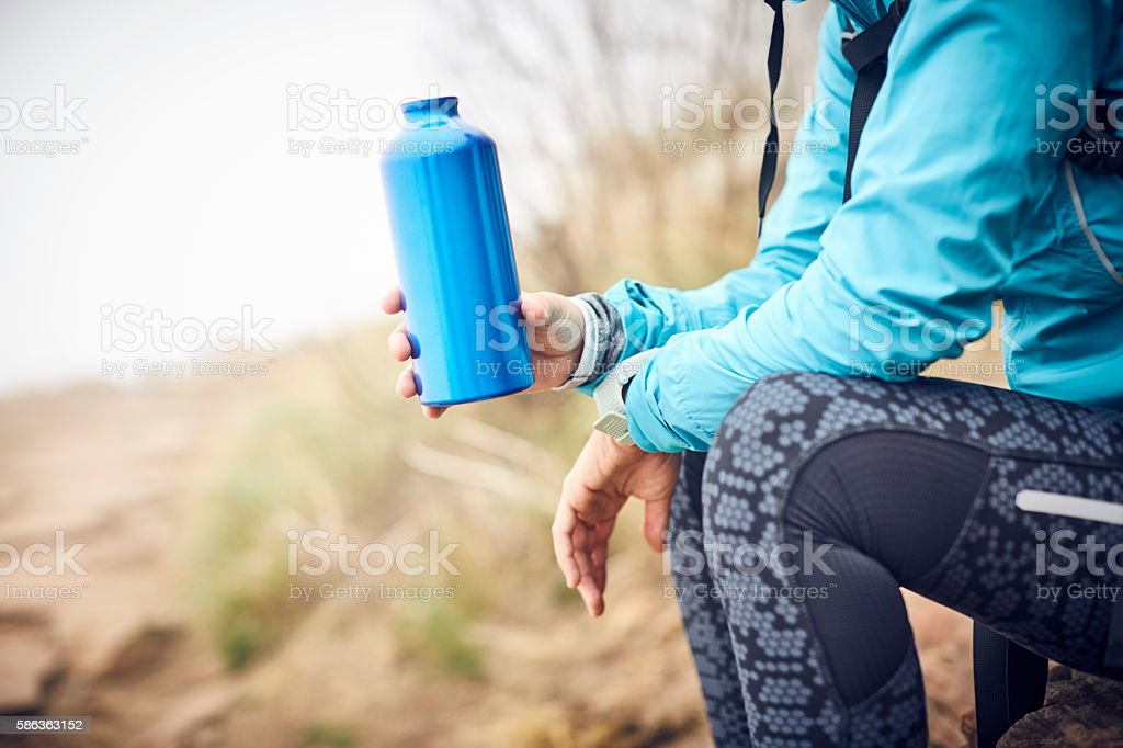 Midsection of female traveler holding water bottle stock photo