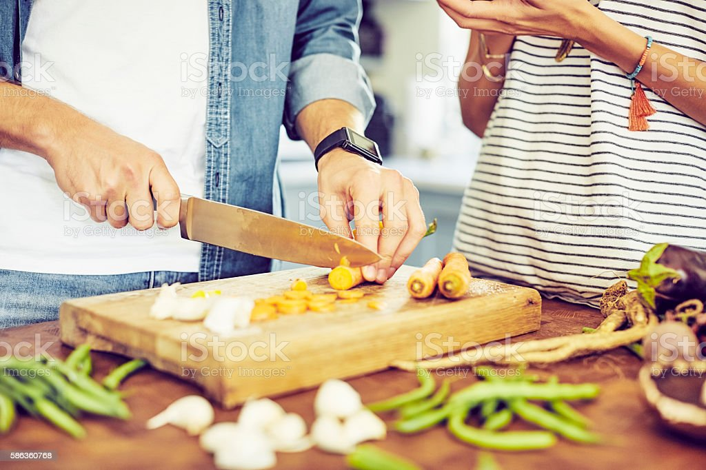 Midsection of man cutting carrots by woman at kitchen island stock photo