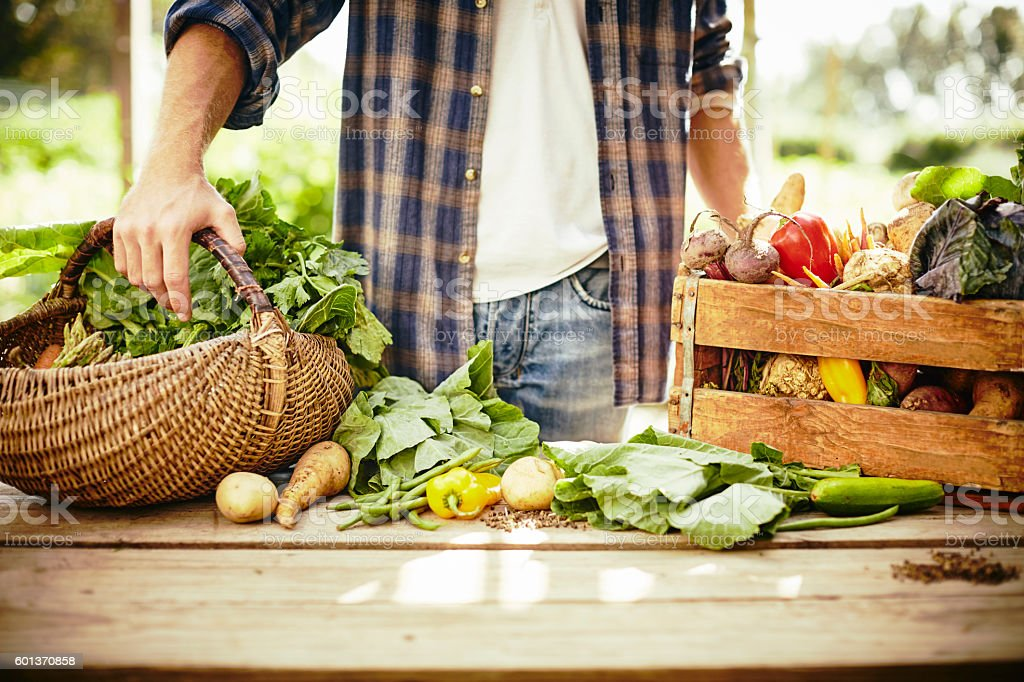 Midsection of man standing with vegetables at table stock photo