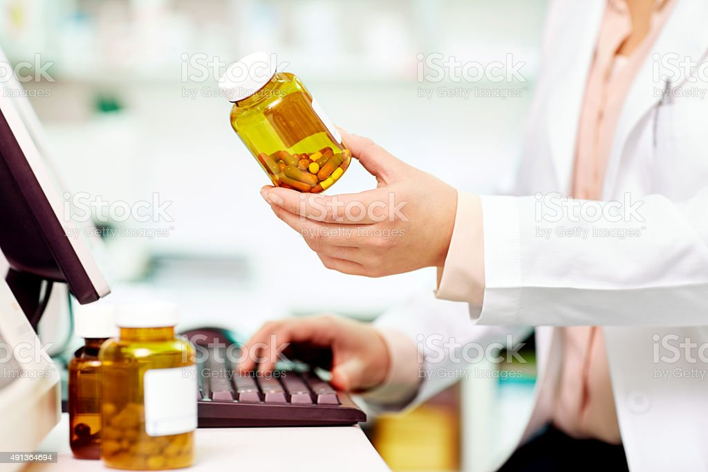Midsection of pharmacist holding pill bottle at computer desk stock photo
