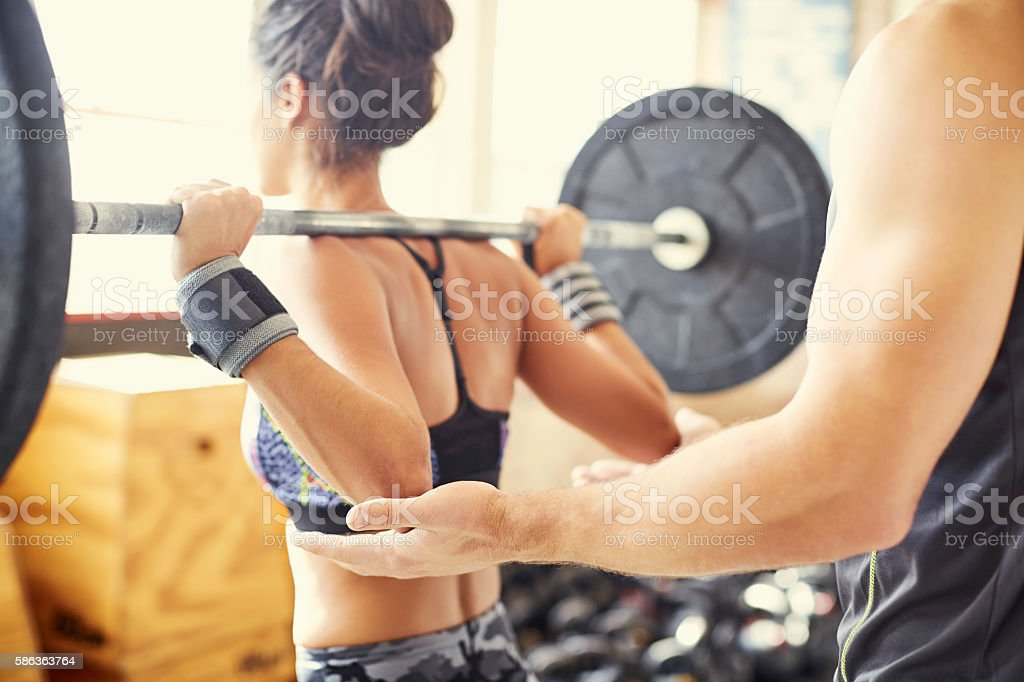 Midsection of trainer assisting customer in lifting barbell in g stock photo