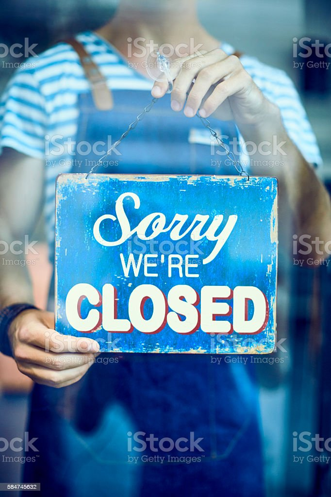 Midsection of waiter holding closed sign at window stock photo