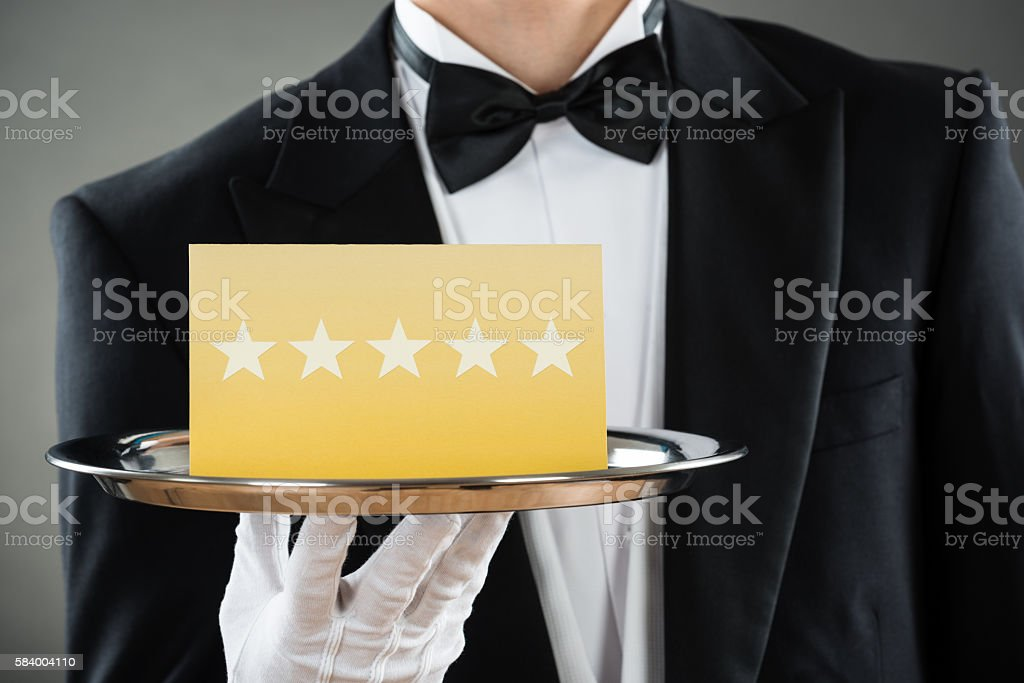 Midsection Of Waiter Holding Tray With Star Rating Label stock photo