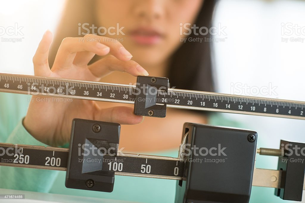 Midsection Of Woman Adjusting Weight Scale stock photo